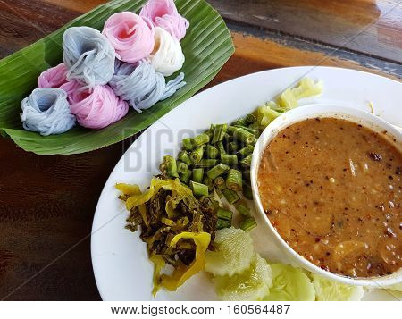 sweet soup with colorful rice vermicelli on banana leaf and vegetables. selective focus