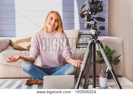 Talented young woman is recording self video at home. She is sitting near sofa and smiling. Blogger is speaking into camera and gesturing
