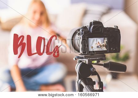 Blog. Happy girl is talking at camera and gesturing. She is sitting at home. Focus on digital device