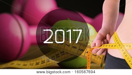 Mid section of woman measuring her waist against 2017 with dumbbells in background