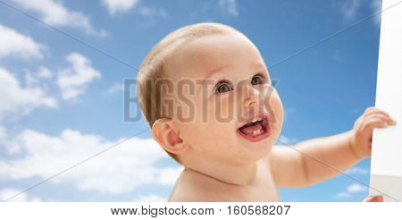 childhood, babyhood, emotions and people concept - happy little baby boy or girl looking up over blue sky and clouds background