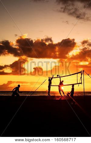Silhouette of beach volleyball players at sunset on Waikiki Beach