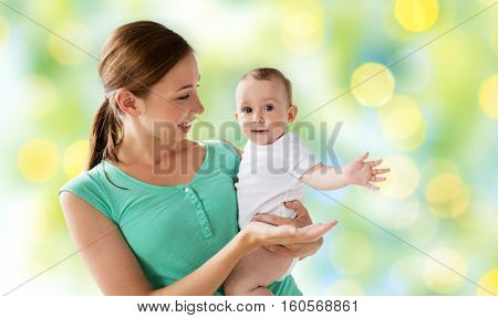 family, child and parenthood concept - happy smiling young mother with little baby over green holidays lights background