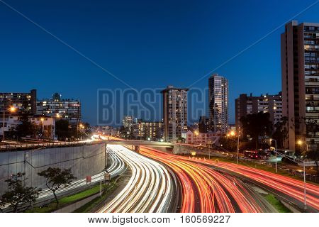 Light streaks over highway, exits and on ramps in downtown, Honolulu at dusk