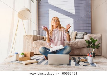 This scent is wonderful. Carefree girl is smelling perfume and smiling. Her eyes are closed with pleasure. Lady is sitting on floor near laptop