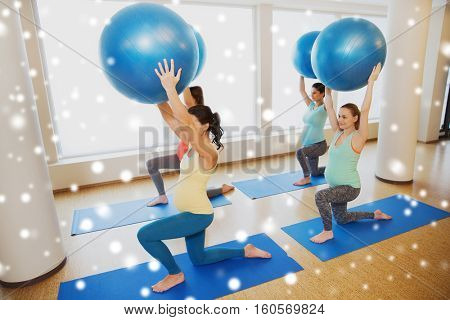 pregnancy, sport, fitness, people and healthy lifestyle concept - group of happy pregnant women exercising with stability balls in gym over snow