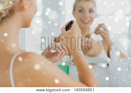 beauty, make up, cosmetics, morning and people concept - close up of young woman makeup brush and powder foundation looking to mirror at home bathroom over snow