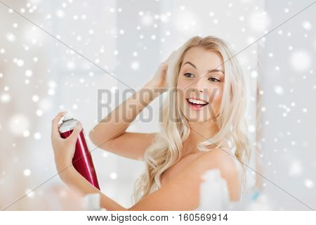 beauty, hygiene, hairstyle, morning and people concept - smiling young woman with hairspray styling her hair and looking to mirror at home bathroom over snow