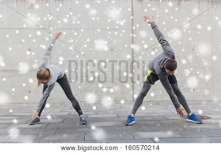 fitness, sport, exercising, training and people concept - couple of sportsmen stretching on city street over snow