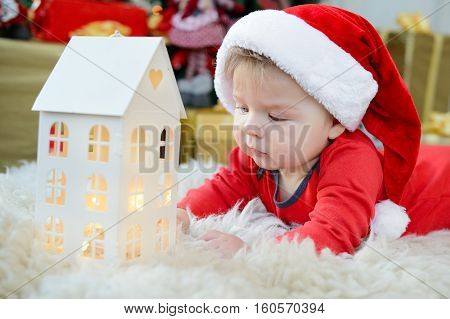 Adorable Portrait Of Cute Little Baby Celebrates Christmas. New Year's Holidays. Boy In A Santa Cost