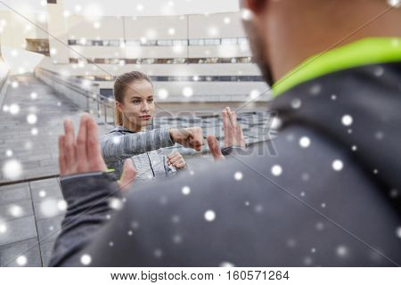 fitness, sport, people, exercising and martial arts concept - young woman with trainer working out self defense strike on city street over snow