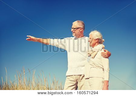 family, age, romance, leisure and people concept - happy senior couple pointing finger to something outdoors