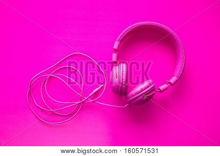 Pink hipster headphones on pink background. Top view.