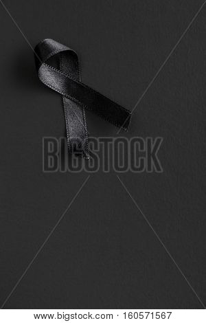 Black satin ribbon on black background. R.I.P. symbol.