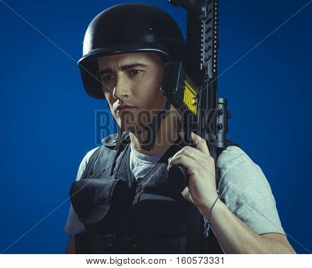 airsoft sport player wearing protective helmet aiming pistol ,black armor and machine gun