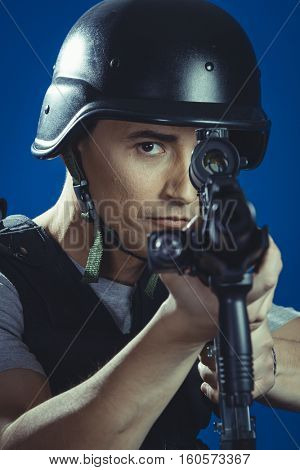 Weapon, paintball sport player wearing protective helmet aiming pistol ,black armor and machine gun