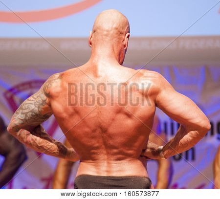 MAASTRICHT THE NETHERLANDS - OCTOBER 25 2015: Male bodybuilder Erik Stobbe flexes his muscles and shows his best physique in a lats spread pose on stage at the World Grandprix Bodybuilding and Fitness of the WBBF-WFF