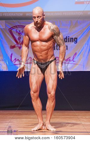 MAASTRICHT THE NETHERLANDS - OCTOBER 25 2015: Male bodybuilder Erik Stobbe flexes his muscles and shows his best physique in a front pose on stage at the World Grandprix Bodybuilding and Fitness of the WBBF-WFF