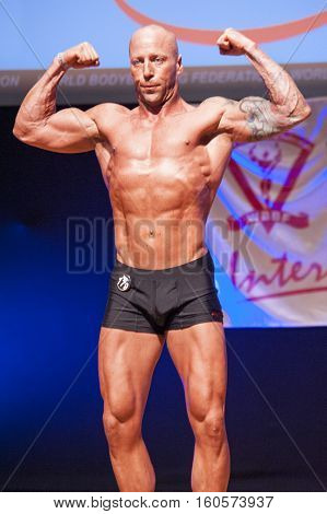 MAASTRICHT THE NETHERLANDS - OCTOBER 25 2015: Male bodybuilder Erik Stobbe shows his best front double biceps pose at the World Grandprix Bodybuilding and Fitness of the WBBF-WFF