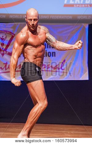 MAASTRICHT THE NETHERLANDS - OCTOBER 25 2015: Male bodybuilder Erik Stobbe shows his best triceps pose at the World Grandprix Bodybuilding and Fitness of the WBBF-WFF