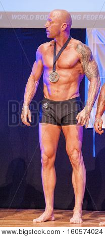 MAASTRICHT THE NETHERLANDS - OCTOBER 25 2015: Male physique model Erik Stobbe celebrates his victory on stage at the World Grandprix Bodybuilding and Fitness of the WBBF-WFF