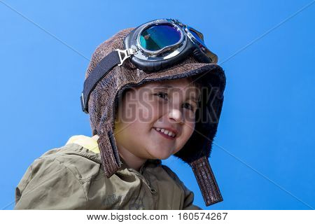 happy aviation, fun and funny child dressed in aviator hat and goggles