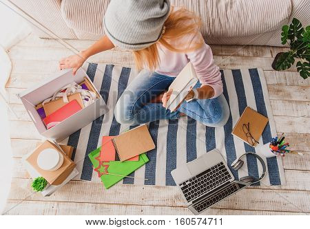 Searching for memories. Top view of young woman taking book and notebooks from box with aspiration