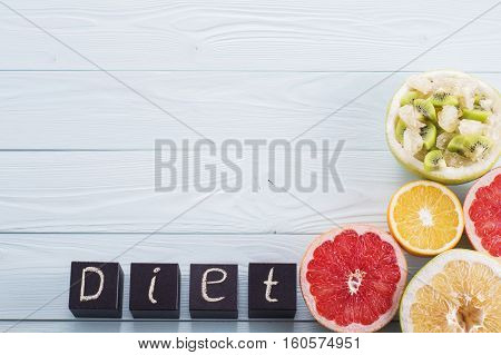 Diet word made with building black wooden blocks with fruit salad and the halves of citrus grapefruit orange sweetie on a blue wooden background with copy space. Diet concept top view.