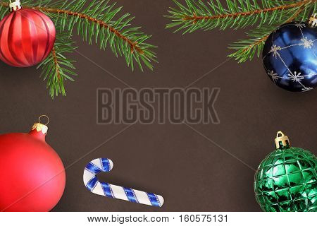 Dark background with Christmas fir branch stick red wavy dull green ribbed and blue ball