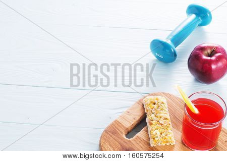 The concept of weight loss jump rope dumbbell juice cereal bar and red apple. Healthy lifestyle. Morning healthy nutrition. Sport and diet.