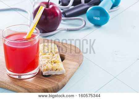 The concept of weight loss jump rope dumbbell juice cereal bar and red apple. Healthy lifestyle. Fitness Background. Sport and diet.