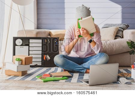 Tired of study. Desperate young girl is covering her face by books. She is sitting on floor near laptop at home