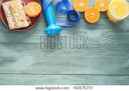 The concept of healthy lifestyle top view with copy space. Orange juice juicy citrus cereal bars dumbbell and measuring tape on green wooden table flat lay. Cereals and fruits - diet and breakfast