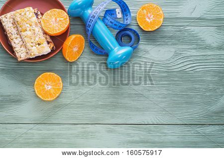 The concept of healthy lifestyle top view. Juicy citrus cereal bars dumbbell and measuring tape on green wooden table flat lay. Cereals and fruits - diet and breakfast