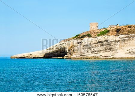 View on blue sea and the tower on the rock in Santa Caterina di Pittinuri in Sardinia Italy.