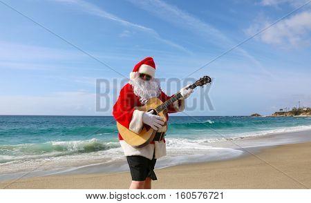 Christmas Santa Claus plays his guitar on the beach.
