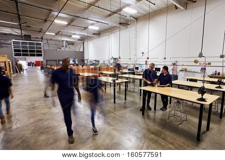 Interior Of Busy Factory With Staff At Work Benches