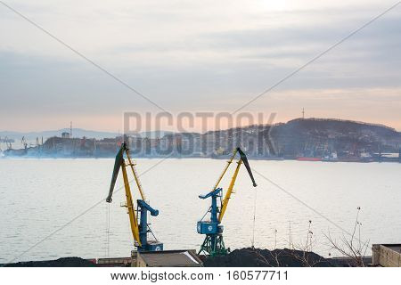 Two crane in the port on sea bay background. Heap of coal and ships Top view.
