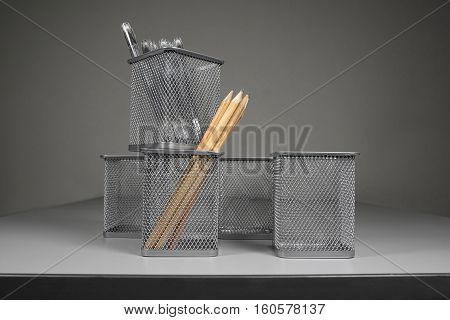 Few stationery holder with pencils and pens. Metallic items.