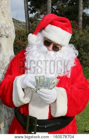 Santa Claus with Money. Santa counts and has lots of money.