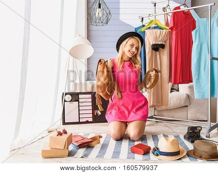Online shopping. Confident young woman is holding leather backpack and belt. She is sitting on floor at home and laughing