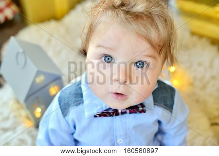 Adorable Close Up Portrait Of Cute Little Baby Boy In Bowtie Celebrates Christmas. New Year's Holida