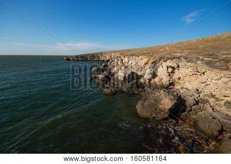Coast of sea with rocks, bright blue sky at summer sunny day