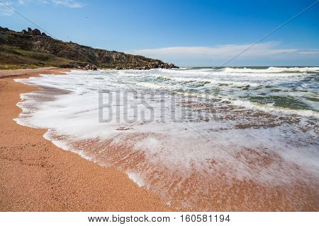 Waterside of sea, foam, blue sky, beach and rocks at summer sunny day