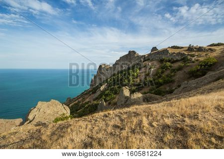 Beautiful rocks near sea waterside, dry grass and blue water at summer day