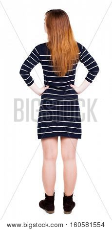 back view of standing young beautiful  woman in dress. girl  watching. Rear view people collection.  Isolated over white background. Adding putting hands on waist stands and looks to the right.