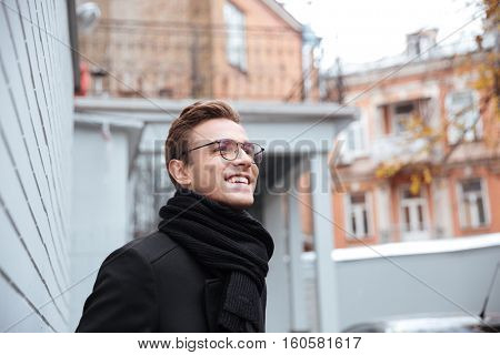 Business man in glasses and warm clothes in courtyard. From below image