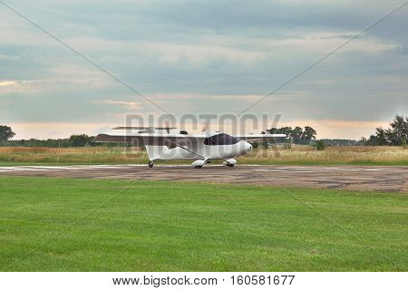 Kiev Region Ukraine - July 19 2014: Light private twin-engine plane is taking off from the runway with stormy sky on sunset on the background