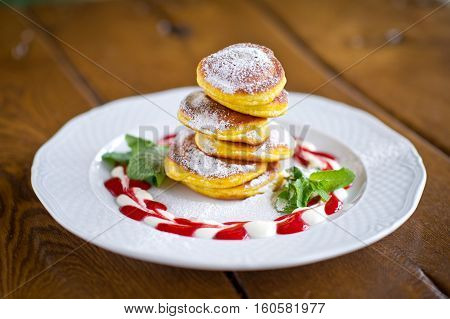 Homemade fritters of cottage cheese with nicely decorated strawberries sauce, sugar powder and mint in white plate on wooden background. Tasty food for kids menu