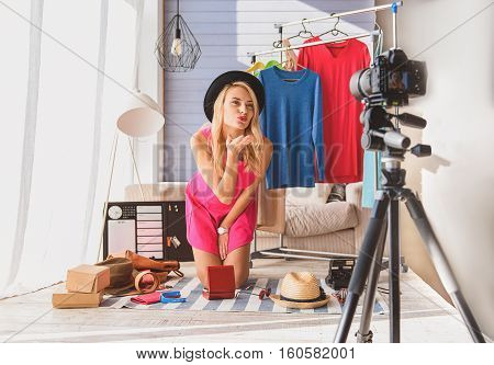 Carefree blond girl is maintaining blog at home. She is wearing fashionable clothing. Lady is sending air kiss to camera with love